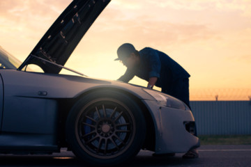 Abstract blurred background of man is checking engine bay of sport car while sunset.