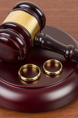 Wooden judge gavel and golden rings divorce concept