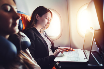 Female entrepreneur working on laptop sitting near window in an airplane