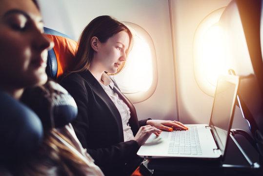 Female entrepreneur working on laptop sitting near window in an airplane