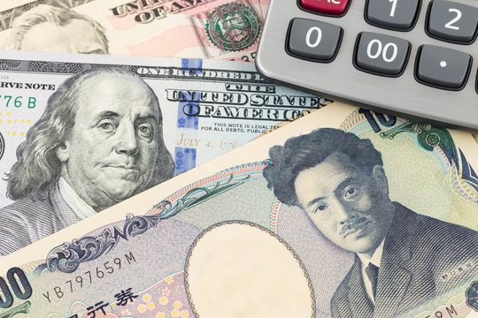 US Dollar and Japanese Yen banknote money with calculator