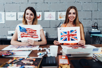 Two smiling female designers of prints showing their works, American and British flags drawn with watercolor technique, sitting at their work desk in creative office
