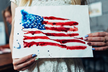 Close-up view of female hands holding a sheet of paper with a hand-darwn watercolor illustration of the flag of the United States