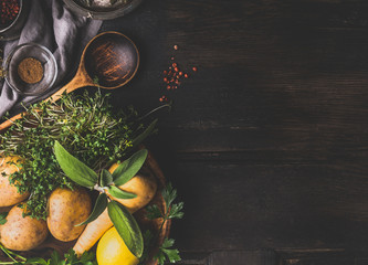 Food and cooking background with vegetables , flavor herbs and cooking spoon on dark rustic background, top view, place for text
