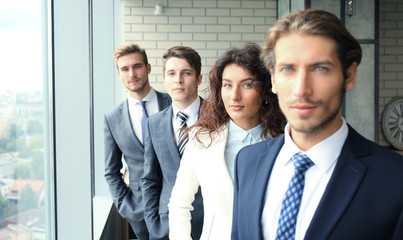 Happy smiling business team standing in a row at office.