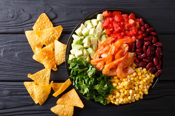 Mexican burrito bowl with shrimp, beans, corn, avocado and herbs closeup. horizontal top view
