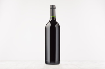 Black wine bottle with red wine on white wooden board, mock up. Template for advertising, design, branding identity.