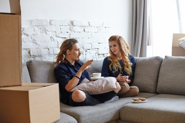 People, property, mortgage and real estate concept. Candid shot of happy trendy looking young couple relaxing on couch in renovated living room, having coffee and discussing interior design in kitchen