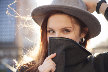 Outdoor portrait. Young stylish pretty woman with hat in hand posing in the big city streets.