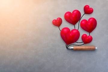 valentine concept with red heart shape object with wooden handle pencil on grey leather background with free copyspace for your creativity ideas text