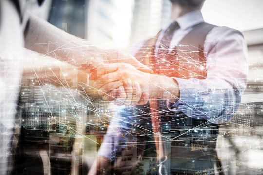 Two business people shaking hands.Successful business people handshaking closing a deal.Agreement Concept.double exposure with cityscape nighttime