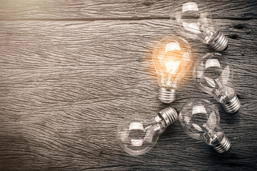 creativity ideas concept with light bulb on wooden texture background
