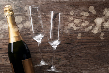 Photo of two wine glasses, bottle of champagne, light spots