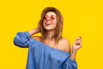 Excited trendy woman laughing on orange