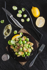 Roasted Brussel Sprouts with Parmesan cheese, lemon, Salt, Pepper on a black table. top view