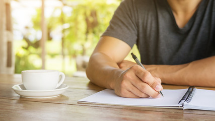 Man writing on a notebook in a cafe.