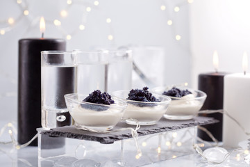 Festive buffet with vodka, black cavier and canddles. Celebration concept for Christmas, new year or other party