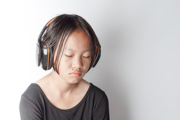 Thai asian little girl listen sad music from headphones