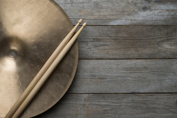 Drum stick and crash cymbal on wood table background, top view, music concept