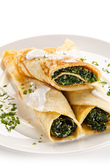 Crepes with spinach and feta cheese on white background
