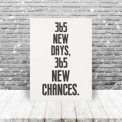 "Inspiration Quote ""365 new days, 365 new chances"" on paper at wooden table top and old brick wall background with snowfall."