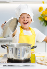 Happy little boy opened the lid on the pan