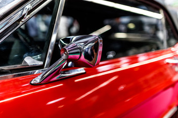 chrome rear-view mirror by the red sports vintage car.