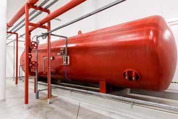 Industrial big red tank inside factory. Tank for water under high pressure. Fire systems.