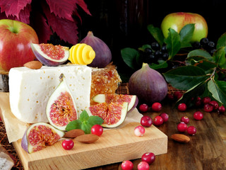 Cheese made of sheep milk and slices of figs on a wooden board surrounded by cranberries, honey and almond. Ingredients for a cheese plate