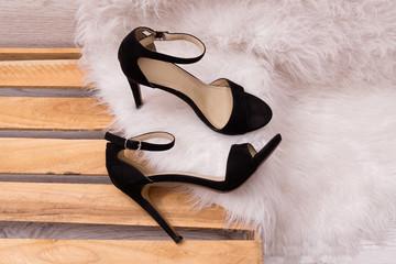 Black shoes on a pallet, white fur. Fashionable concept