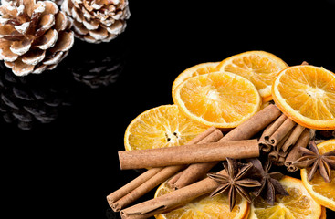 Keuken foto achterwand Plakjes fruit Dried slice of orange, cinnamon stick, star anise and pine cones on black background.