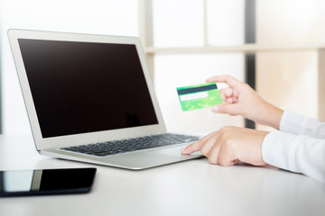 Closeup of happy young woman holding credit card inputting information while and using laptop computer at home. Online shopping concept.