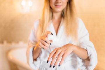 Female person in bathrobe, skincare in bathroom
