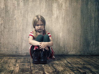 Sad little girl sitting on the floor. Textured grey wall
