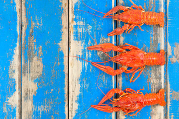 Row of three whole red boiled crawfish on old rustic blue wooden planks