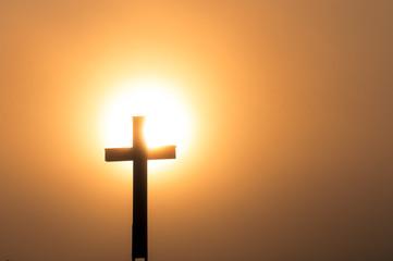 Catholic cross in sundown, dense fog.