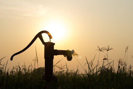 The silhouette water pump on the grass and rice field with the sun on the evening , with copy space