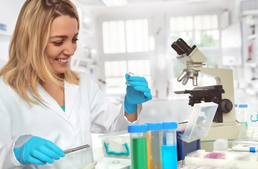 Female scientist in lab coat and protective gloves ilaughts while looking at glass vial