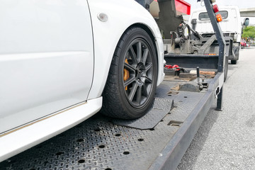 Car towed onto flatbed tow truck with hook and chain