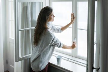 Woman in warm woolen pullover is opening window