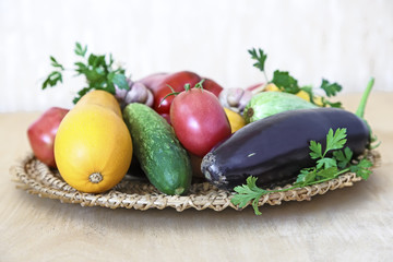 Various vegetables on a wicker dish on the table.