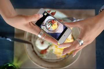 Young woman taking photo of delicious food with mobile phone