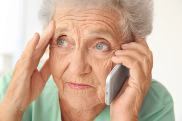 Elderly woman speaking on cell phone at home