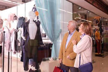 Elderly couple window shopping in mall