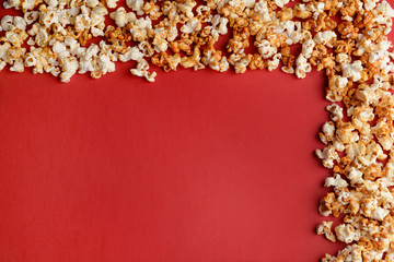 Frame made of tasty caramel popcorn on color background