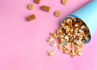 Paper cone with tasty caramel popcorn on color background