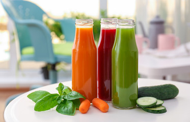 Bottles with various fresh vegetable juices on table