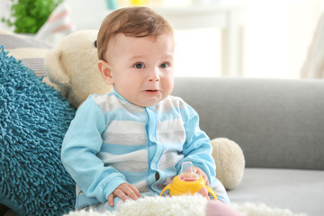 Cute baby with bottle of water sitting on sofa at home
