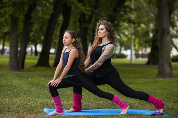 Family teamwork gymnastics. Active females lifestyle. Yoga exercise outdoors, healthy beauty, teenage sport with coach. Nature background, entertainment outside