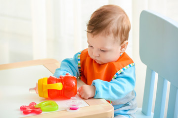 Cute little baby with bottle of water sitting at table in room